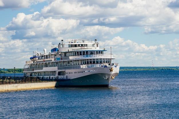 Altes und weißes kreuzfahrtschiff am pier.