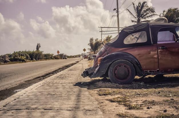 Altes verlassenes auto an der seite einer straße von isla mujeres