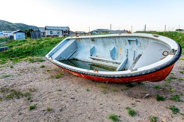Altes verlassenes boot auf dem ufer.