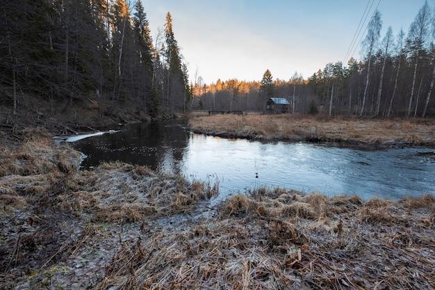 Altes verlassenes holzhaus am fluss im nördlichen wald im spätherbst