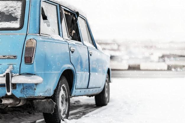 Altes verlassenes kombiwagenblau des scheinwerfers in der farbe mit defekten fenstern. geparkt auf der seite einer winterstraße im schnee in russland. kopieren sie platz