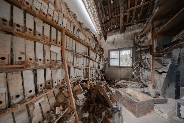 Altes verlassenes lagerhaus mit einem zerstörten regal voller dokumente
