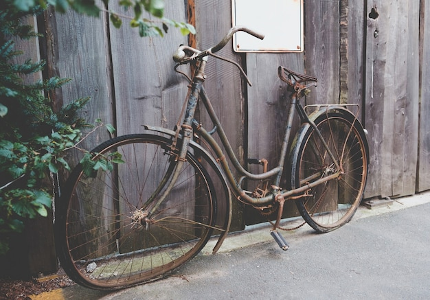 Altes verrostetes fahrrad, das an der straße steht