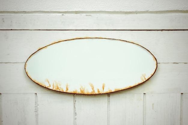 Altes verrostetes ovales eisenzeichen, das am hintergrund eines weißen holzfußbodens hängt