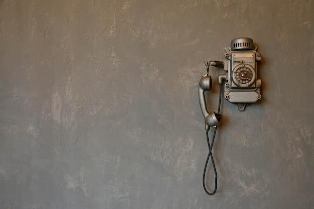 Altes vintage-kabeltelefon für die kommunikation hängt an der strukturierten grauen wand. antikes telefon aus der vergangenheit für den hintergrund. geschichte des telefons in der welt. konzept der kommunikation und des telegrafen. platz kopieren
