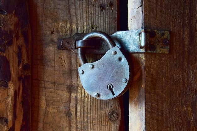 Altes vorhängeschloss an einer holztür in einem landhaus. nahansicht.