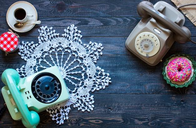 Altes weinlese-telefon, mit biscotti, donuts auf einem hölzernen hintergrund, freier raum für text