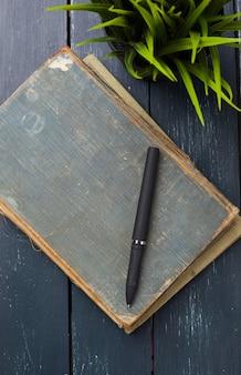 Altes weinlesebuch auf hölzernem schreibtisch