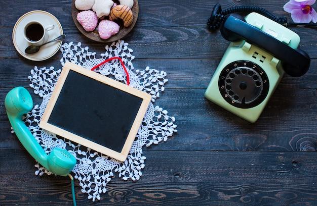 Altes weinlesetelefon mit biscottikaffeeschaumgummiringen auf einem hölzernen hintergrund