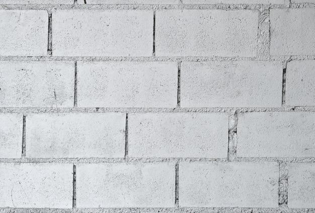 Altes weiß gemalter zementbacksteinblockmauerbeschaffenheits-oberflächenhintergrund.