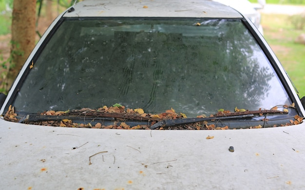 Altes weißes auto mit flecken. schmutz auf der glasauto verschmutzung, oberflächenschmutz, staubbodenbeschaffenheits-zusammenfassungshintergrund.