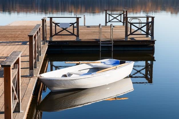 Altes weißes boot mit blauen rudern nahe dem hölzernen pier auf dem ufer von einem waldsee. sonniger herbsttag