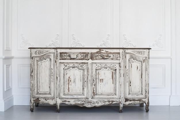 Altes weißes kommodenbüro mit der farbe abgezogen auf luxuswanddesignflachreliefstuckformteil-roccocoelementen