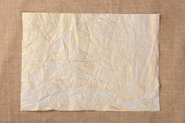 Altes zerknittertes papierblatt auf segeltuchsackleinen.