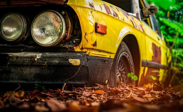 Altes zerstörtes auto im weinlesestil. verlassenes rostgelbes auto im wald