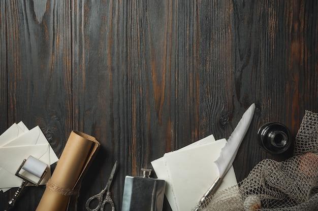 Altmodische flache lage mit buchstaben, die zubehör auf dunklem holzhintergrund schreiben. weiße blätter, feder, signet, verpackung, tinte. vintage-stil, steampunk, gaslight-konzept. exemplar für vorschlag.