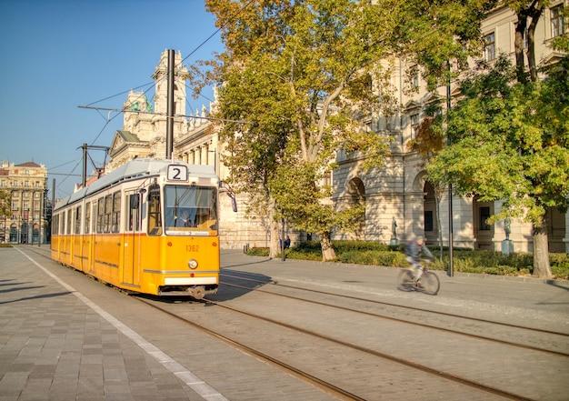 Altmodische gelbe straßenbahn, die sich an einem klaren sonnigen herbsttag entlang des historischen teils der stadtstraße in budapest, ungarn, bewegt.