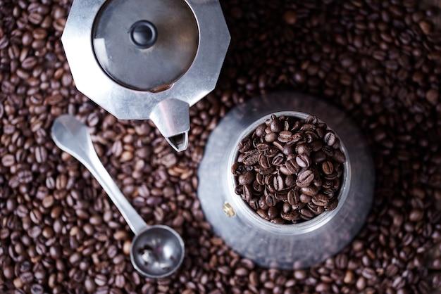 Altmodische kaffeemühle unter kaffeebohnen