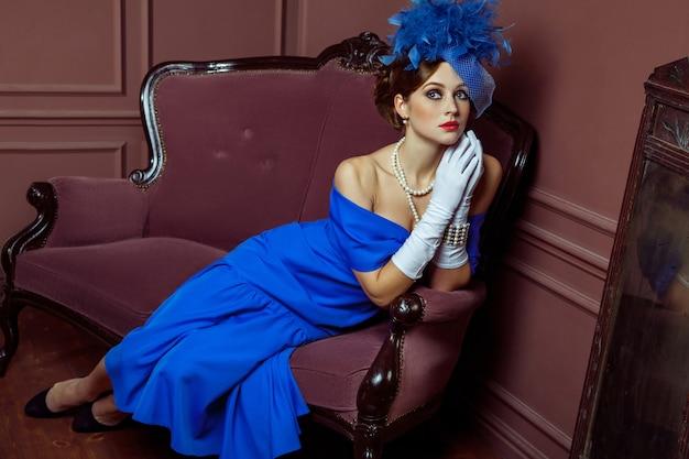Altmodische retro-fotografie im britischen stil. schönes junges kaukasisches modell in blauem kleid und mode-make-up und hut posiert auf dem künstlichen sofa sitzend und schaut in die ferne.
