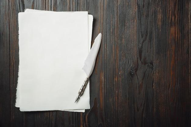 Altmodische wohnung mit briefen oder büchern, romane, die accessoires auf dunklem holztisch schreiben. stift und weiße blätter. vintage-stil, steampunk, gaslight-konzept.