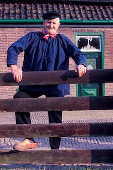 Altmodischer älterer mann in der traditionellen kleidung und in den hölzernen clogs, die nahen zaun stehen
