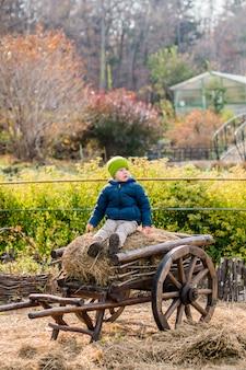 Altmodischer kleiner junge, der an einem weinleseholzwagen sitzt