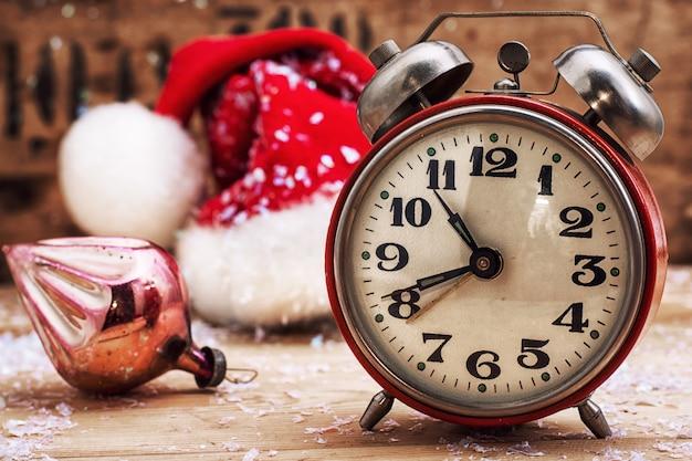 Altmodischer wecker und rote weihnachtskappe