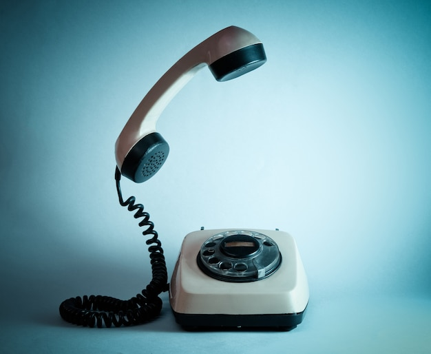 Altmodisches drehtelefon mit schwebendem telefongriff, blaues neonlicht, 80er jahre