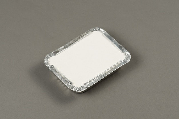 Aluminiumbehälter zum mitnehmen von warmen speisen, die zur lieferung auf grauem hintergrund zubereitet werden