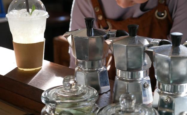 Aluminiumkanne kaffeemaschine auf bartheke & barista im café.