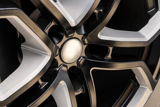 Aluminiumlegierungsrad. premium cast, das design der speichen und der felge, weiße und schwarze elemente auf dunklem hintergrund nahaufnahme