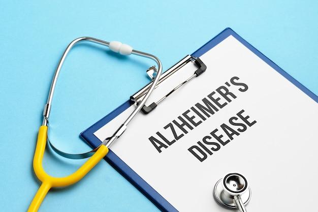 Alzheimer-krankheitsdiagnosekonzept auf medizinischer tablette mit dokumenten mit stethoskop.