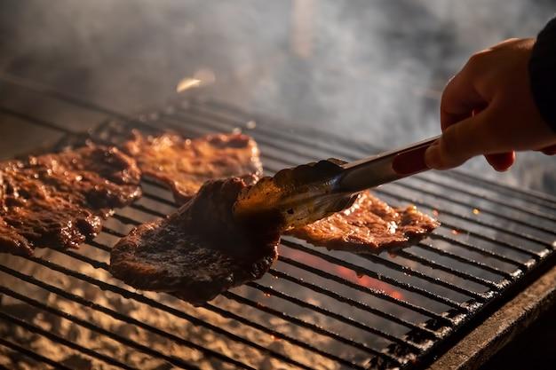Am abend ein barbecue-grill, auf dem leckere saftige steaks über offenem feuer gegrillt werden eine hand