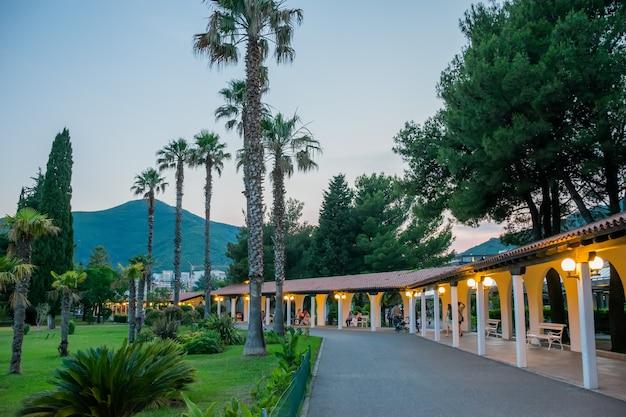 Am abend spazieren touristen durch den wunderschönen park von budva.
