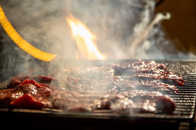 Am abend werden köstliche saftige steaks auf offenem feuer auf einem grillgrill nahaufnahme weich gegrillt
