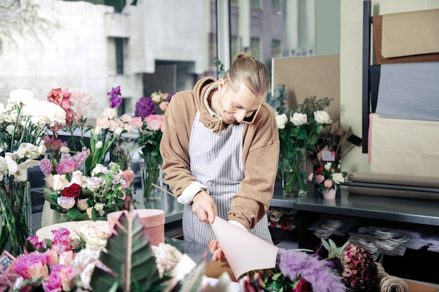 Am arbeitsplatz. hübsche männliche person, die positivität ausdrückt, während sie im blumenladen arbeitet