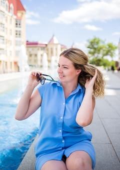 Am brunnen sitzt eine junge frau in blauem kleid mit sonnenbrille. sommer hintergrund