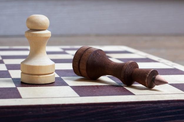 Am ende des schachspiels besiegte der weiße bauer den dunklen könig. der gefallene schachkönig als metapher für den fall der macht. geschäftskonzept kopienraum, selektiver fokus