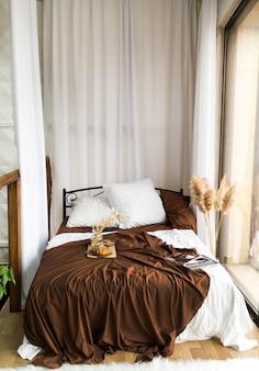 Am fenster steht ein altes, stilvolles bett mit brauner tagesdecke und weißer bettwäsche. getrocknete blumen in einer vase, zeitschriften, croissants und brauner zucker für tee. vertikales foto