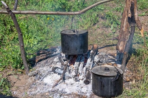Am feuer werden zwei töpfe mit essen zubereitet. abenteuerreisender lebensstil. konzept fernweh. aktive wochenendferien wilde natur im freien. sommer.