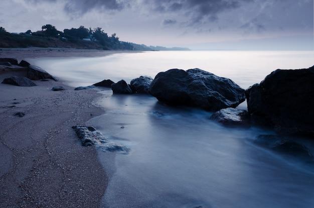 Am frühen morgen an der felsigen küste des meeres. glattes wasser des meeres wegen der langen belichtung. zeit vor sonnenaufgang.