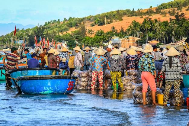 Am frühen morgen fischerdorf in mui ne, voller vietnamesischer verkäufer am strand