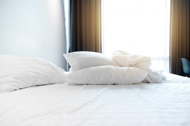 Am frühen morgen in einem weißen schlafzimmer mit zerknitterter steppdecke und kissen auf dem bett.