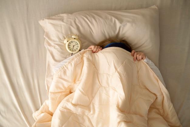 Am frühen morgen liegt ein mädchen im bett unter der decke neben dem wecker, den das mädchen schlafen möchte