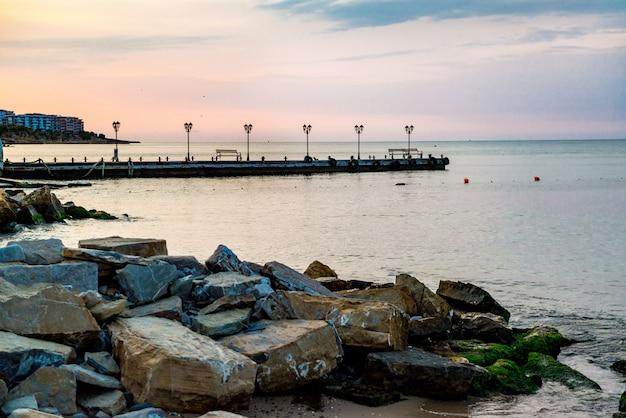 Am frühen morgen sonnenaufgang über dem meer. pier auf dem betonwall