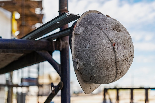 Am gerüst hängt ein alter arbeitshelm. unscharfer hintergrund. konzept der harten arbeit des builders.