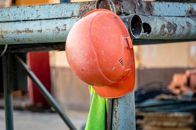 Am gerüst hängt ein orangefarbener arbeitshelm mit signalweste. unscharfer hintergrund. bauarbeiten einbrechen.
