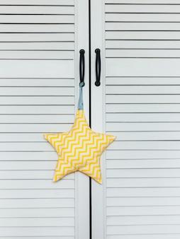 Am griff eines weißen kabinettschirms hängt eine nahaufnahme eines weißgelben spielzeugs mit weichen sternen. helles interieur