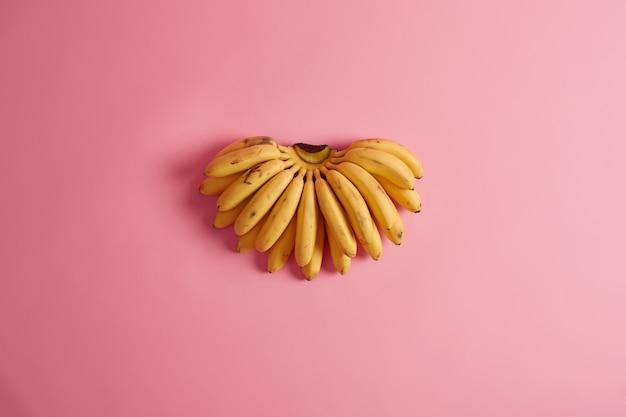 Am häufigsten konsumierte früchte. ein bündel gelber bananen, die eine große auswahl an kalium, vitaminen, mineralien und antioxidantien enthalten, kann teil ihres gesunden lebensstils sein. wichtige nahrungspflanze.