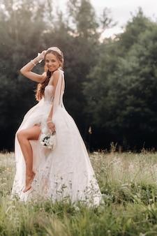 Am hochzeitstag steht eine elegante braut in einem weißen langen kleid und handschuhen mit einem blumenstrauß in den händen auf einer lichtung und genießt die natur. weißrussland.